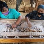 Foto: Pekerja perempuan di Jepara sedang menghaluskan permukaan hasil kerajinan ukiran secara detail dengan amplas