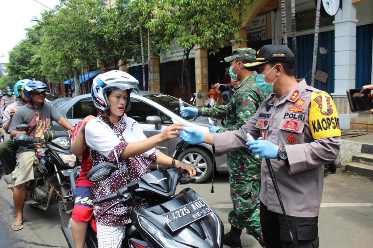 Petugas membagikan hand sanitizer kepada pengguna jalan
