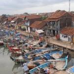 Perahu nelayan berukuran kecil, bersandar di sepanjang sungai.